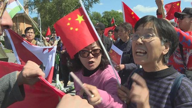 Une femme brandissant un drapeau chinois crie vers un autre manifestant dans une foule.