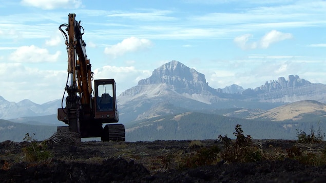 Une pelle mécanique inoccupée aux environs du mont Grassy, avec le mont Crowsnest en arrière-plan, photographié en 2014.