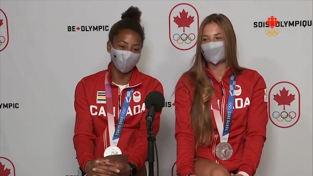 Jennifer Abel et Mélissa Citrini-Beaulieu portent leur médaille d'argent devant un microphone.