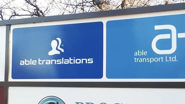 Les logos sont blancs sur fond bleu. Able Translations avec 2 silhouettes de visages et Able Transports avec la lettre A en minuscule.