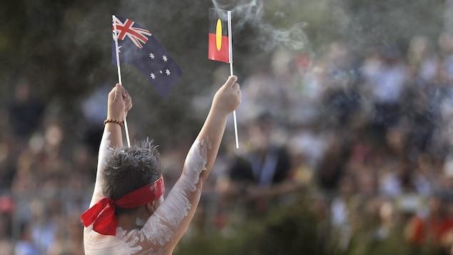 Un jeune Aborigène tient les drapeaux de l'Australie et des Aborigènes lors de célébrations en janvier 2020.