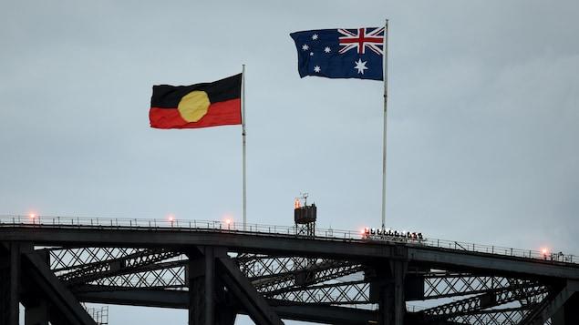 Deux drapeaux flottent au-dessus d'un pont.