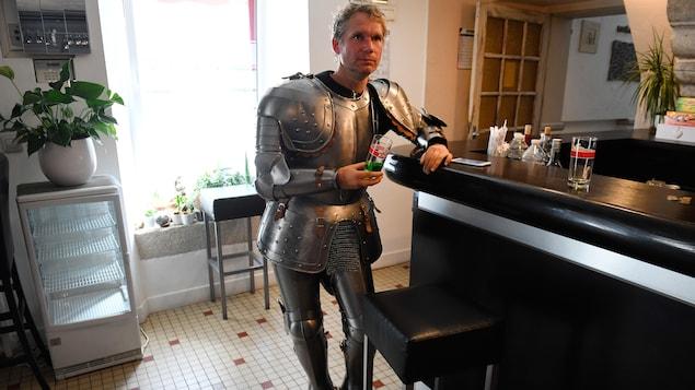 L'artiste français Abraham Poincheval est dans un bar, un verre à la main, vêtu d'une armure de 34 kilos.