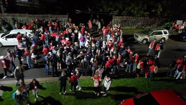 Des centaines de personnes dans une rue résidentielle.