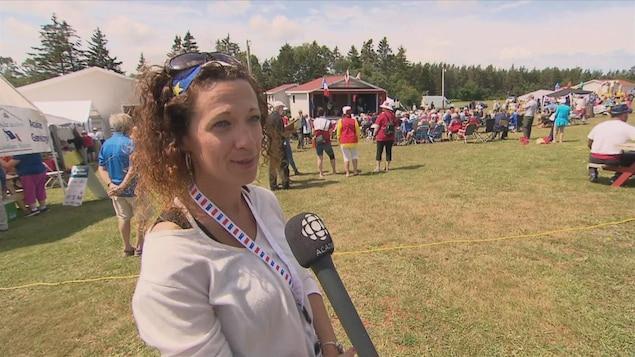 Une femme parle devant la caméra et on voit à l'arrière les célébrations acadiennes.