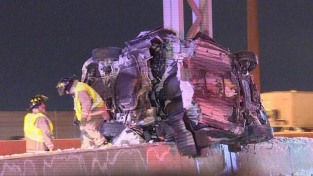 Une voiture écrasée contre un poteau sur l'autoroute 401