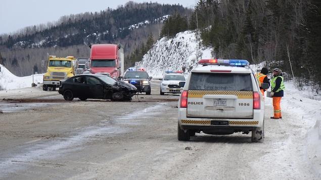 Des voitures de police bloquent la route. Au centre des voies, un véhicule noir est fortement endommagé.