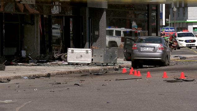 Scène d'accident sur le boulevard Charest Ouest, à Québec. On aperçoit un véhicule de police, une voiture accidentée de couleur grise, des éclats de verre, de plastique et de métal ainsi que de petits cônes orange déposés sur la chaussée.