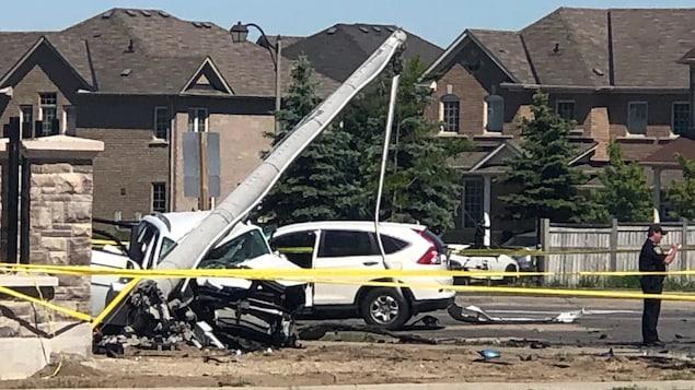Un véhicule écrasé sous un poteau sur les lieux d'un accident.