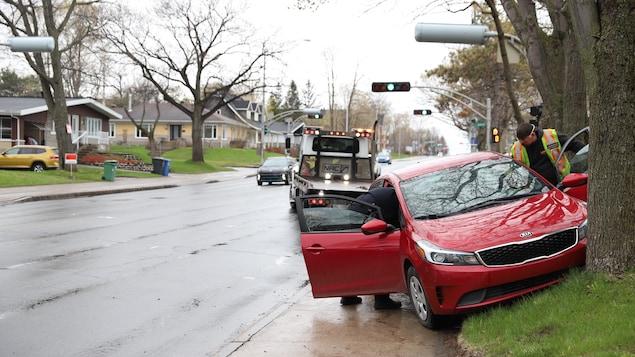 Une voiture rouge de marque Kia est immobilisée après avoir percuté un arbre. L'opérateur d'une dépanneuse s'apprête à remorquer le véhicule.