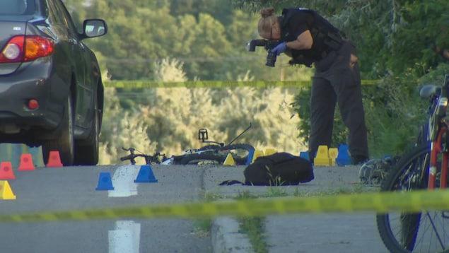 Une enquêteuse prend des photos la scène après une collision entre une voiture et un cycliste, boulevard Jeanne D'Arc, à Ottawa.