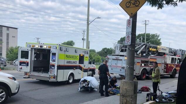 Les ambulanciers offrent les premiers soins au cycliste.