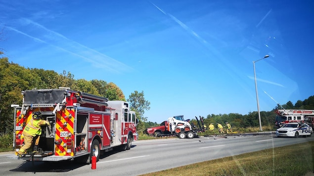 Des camions de pompiers et une voiture de police près des lieux d'un accident de la route.