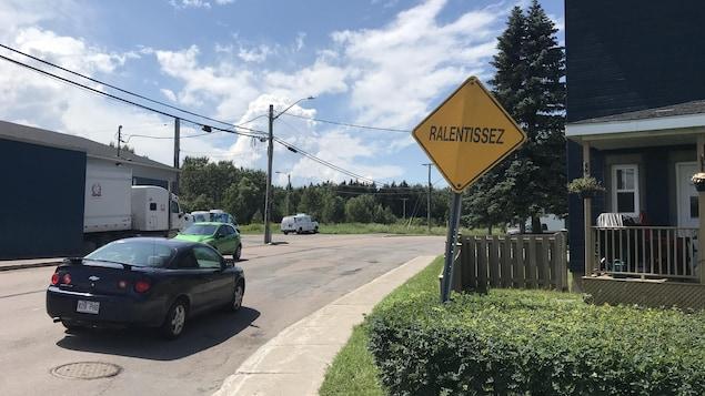 """Une voiture qui roule devant un panneau sur lequel il est inscrit """"ralentissez""""."""
