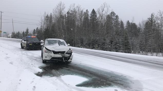 Un véhicule accidenté sur une chaussée enneigée.