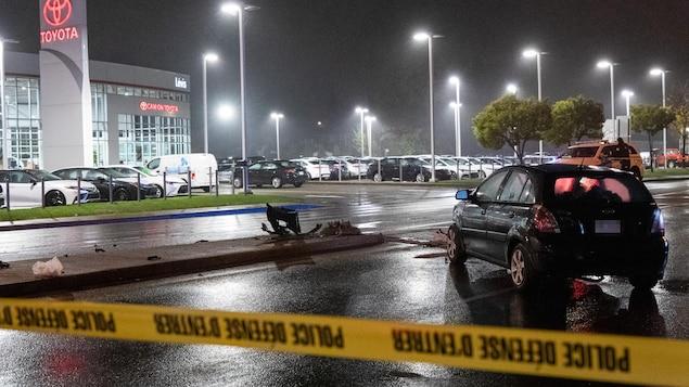 La scène d'un accident, la nuit, sur un boulevard. Un ruban jaune de police ceinture une voiture accidentée.