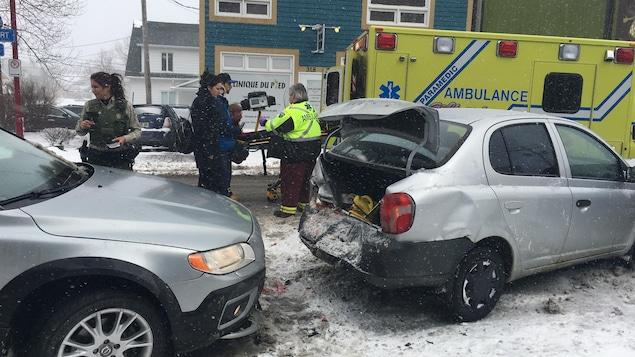 Voiture accidentée, une policière qui marche vers une voiture et des ambulanciers qui roulent une civière vers les portes de l'ambulance.