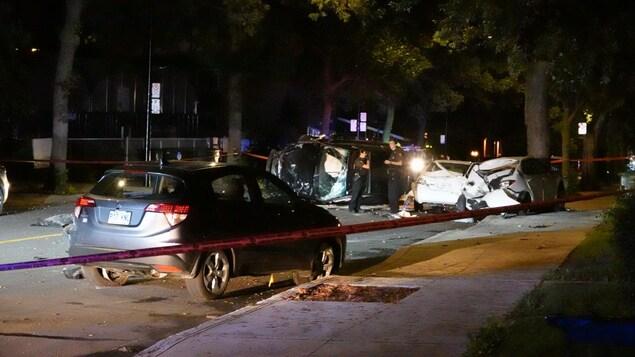 Des policiers sur les lieux d'un accident, où l'on voit plusieurs véhicules endommagés, dont un est renversé sur le côté.