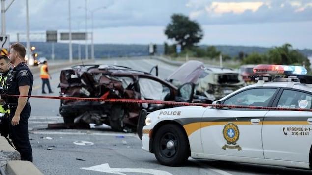 Scène d'un accident de voiture. On voit une voiture complètement cabossée et cassée de partout, une autopatrouille de police et des policiers en uniforme dans un périmètre délimité par un ruban interdisant le passage. Des Débris jonchent le sol.