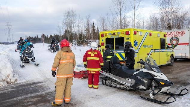 Des pompiers et des ambulanciers se tiennent près d'une motoneige vide.