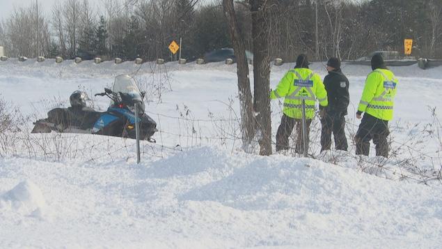 Des agents provinciaux et un policier sur un terrain enneigé près d'un motoneige
