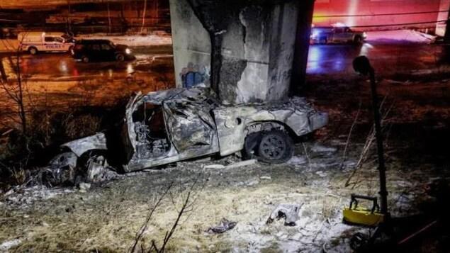 La carcasse d'une voiture sur le bord d'un viaduc
