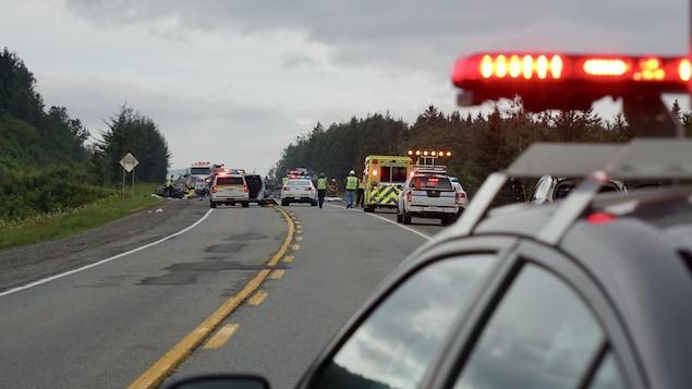 Gyrophares avec voitures accidentées et voiture de police au loin.