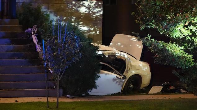 Un véhicule lourdement endommagé encastré dans un immeuble.