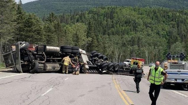 Un camion renversé sur la chaussée avec des secouristes autour.