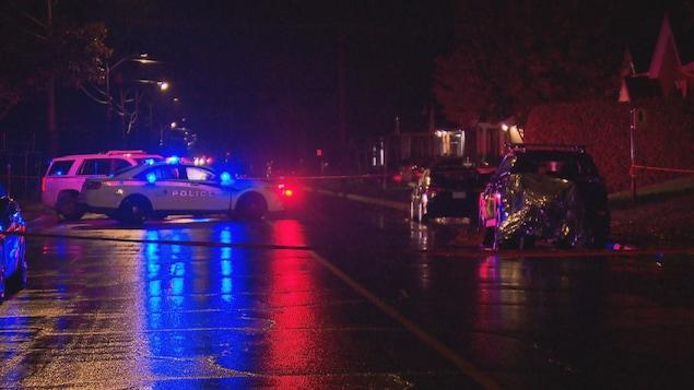 Une rue de nuit bordée de maisons. Deux voitures de police sont au milieu de la voie, les gyrophares allumés.