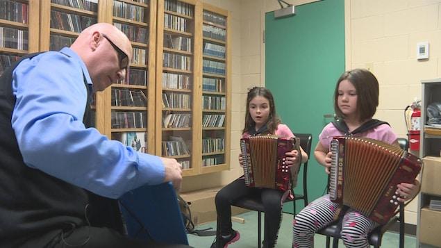 Deux fillettes sont assises sur des chaises. Elles jouent de l'accordéon. Leur professeur est assis en face d'elles.