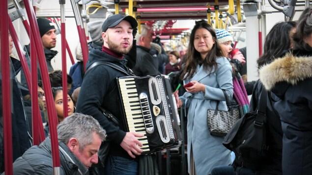 Photo d'un jeune homme qui joue de l'accordéon dans  une rame de métro bondée
