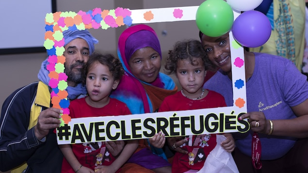 Une famille de réfugiés comprenant un père, une mère et deux enfants, ainsi qu'une femme portant unt-chirt de l'Accueil francophone, font la pose en se tenant derrière un faux cadre de photo géant, sur lequel on peut lire les mots :  avec les réfugiés.
