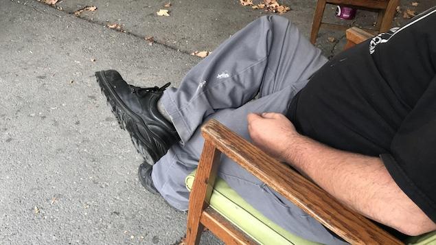 Un sans-abri dont on ne voit pas le visage est assis sur une chaise à l'extérieur.
