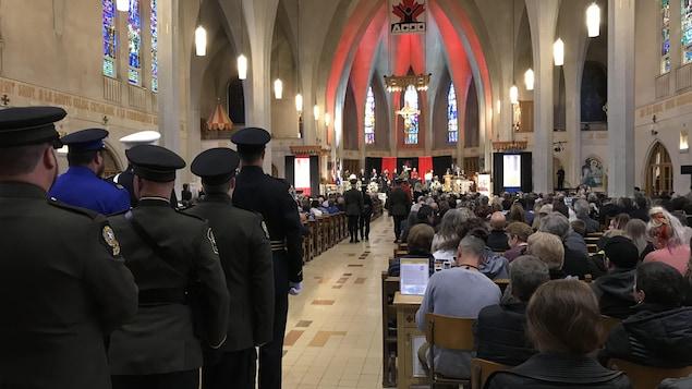 Des personnes assises dans la cathédrale de Sherbrooke. À l'arrière, des militaires attendent de faire leur entrée.