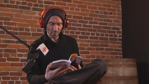 Rémi Francoeur qui tient un livre et lit devant un micro de Radio-Canada.