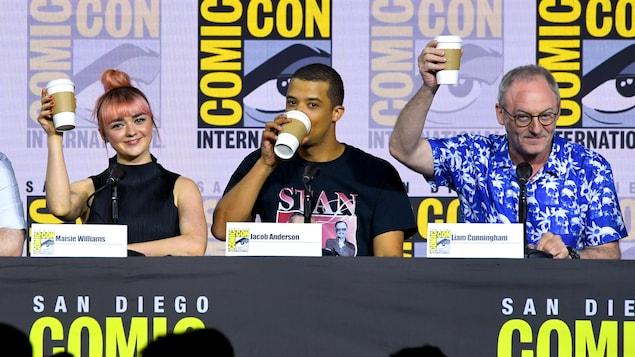 Les trois acteurs, à une conférence de presse au Comic-Con de San Diego, lèvent chacun une tasse de café jetable.
