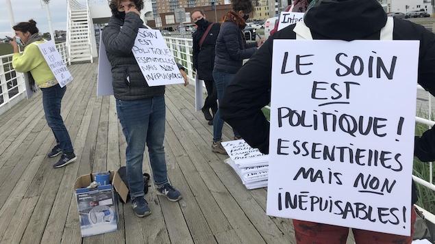 Des femmes tiennent des pancartes entre leurs mains. On peut lire : le soin est politique. Essentielles mais non inépuisables.