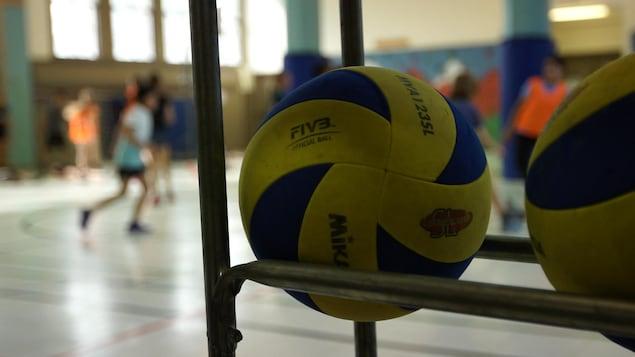 On voit des ballons en avant-plan. Les enfants sont flous à l'arrière.