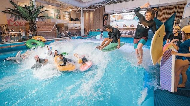 Six garçons surfent sur une vague artificielle.