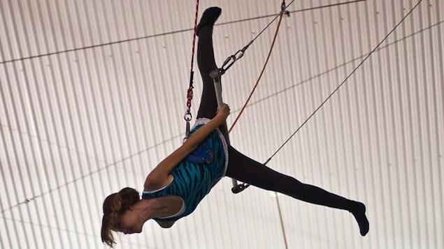 Une jeune fille fait du trapèze volant.