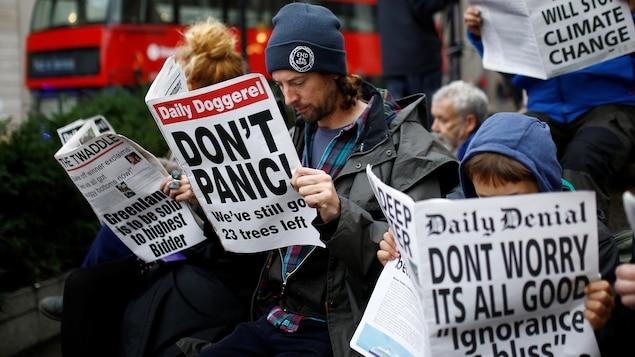 Des manifestants lisent de faux journaux satiriques à Londres, en Angleterre, le 14 octobre 2019.