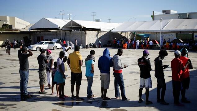 Des migrants font la queue dans un camp.