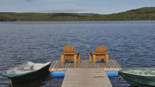 Deux chaises de style Adirondack se trouvent sur le quai d'un lac. Deux chaloupes flottent de chaque côté.