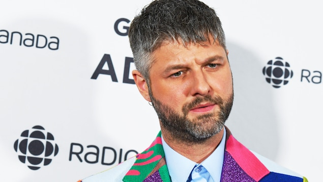 Un homme avec un regard sérieux, est vêtu d'un veston avec plusieurs textures, plusieurs formes géométriques et plusieurs couleurs vives.