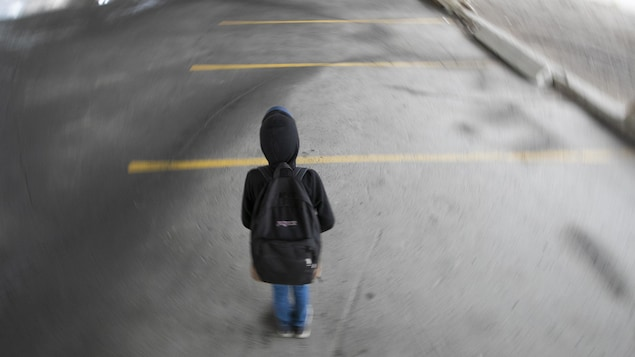 Un adolescent marche seul dans un stationnement désert.