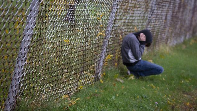 Un jeune adolescent accroupi et adossé à une clôture se prend la tête entre les mains.