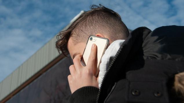 Un adolescent aux cheveux coupés très courts à la nuque, vu de profil, presse un téléphone cellulaire sur son oreille.