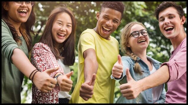 Des adolescents qui lèvent le pouce en l'air et sourient