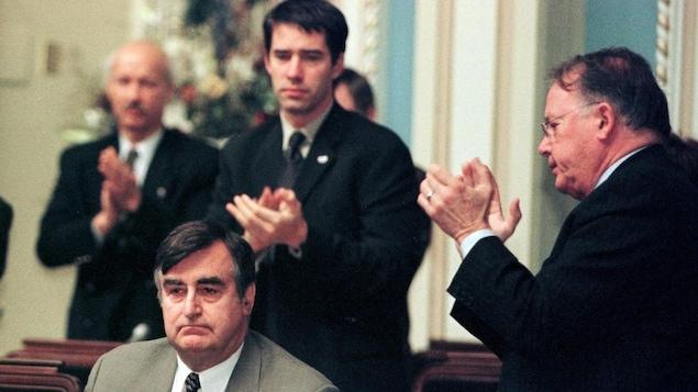 Les ministre péquistes Bernard Landry et André Boisclair applaudissent Lucien Bouchard à l'Assemblée nationale.